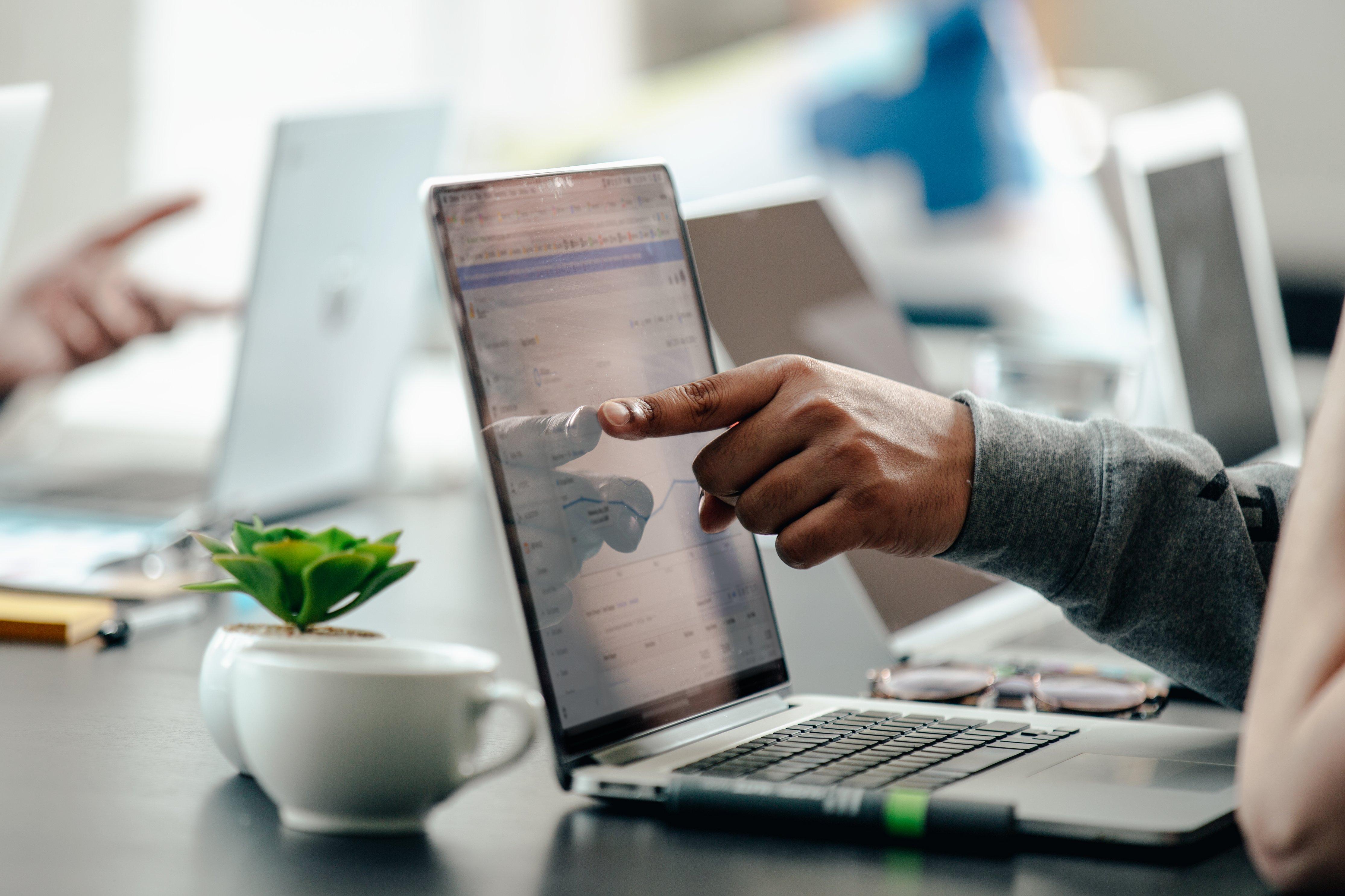 man-pointing-at-laptop-screen-analytics